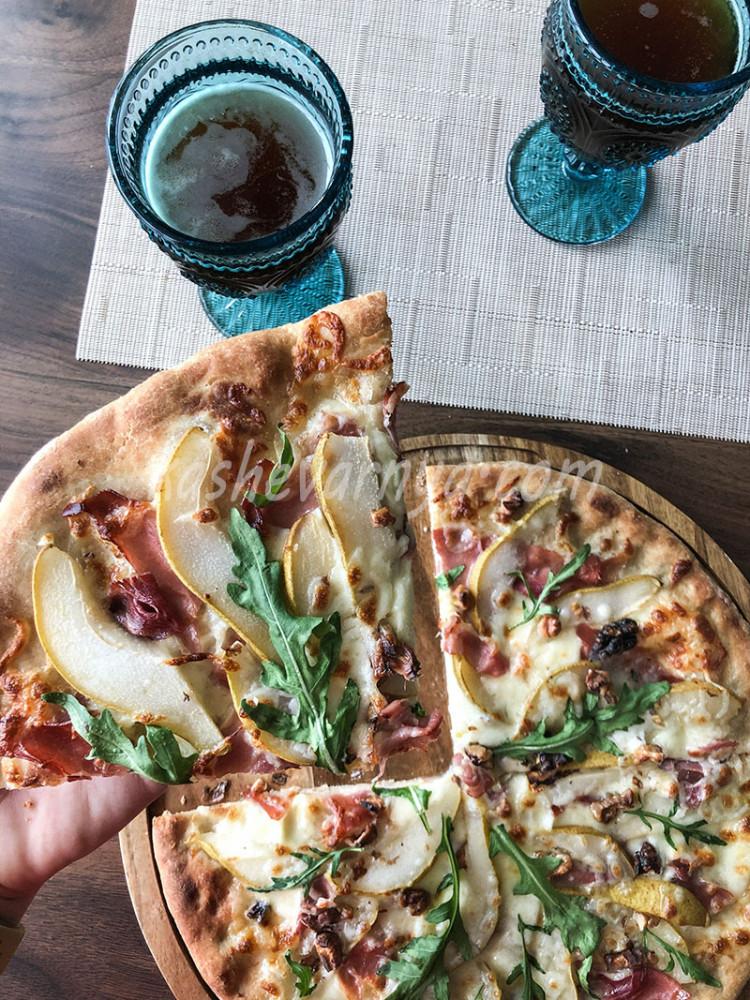 Пицца с грушей, ветчиной, рукколой и орехами